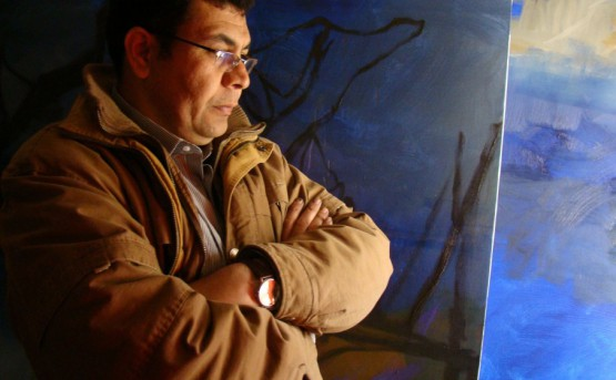Artist Kadhim Nwir stands in front of his works.