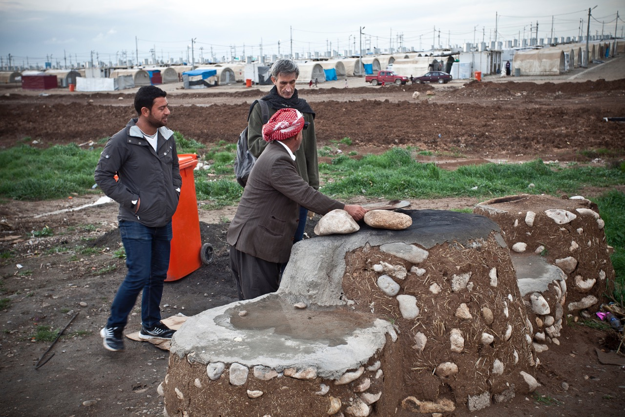 Resident of Camp Shariya, the largest IDP camp in Iraq, shows Francis Alÿs a traditional clay oven. Photo: Akam Shex Hadi/Ruya Foundation.