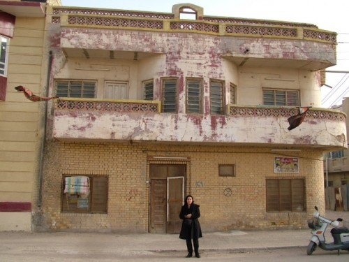 Aleiby stands outside her family home in Basra in 2004. Courtesy of the artist.