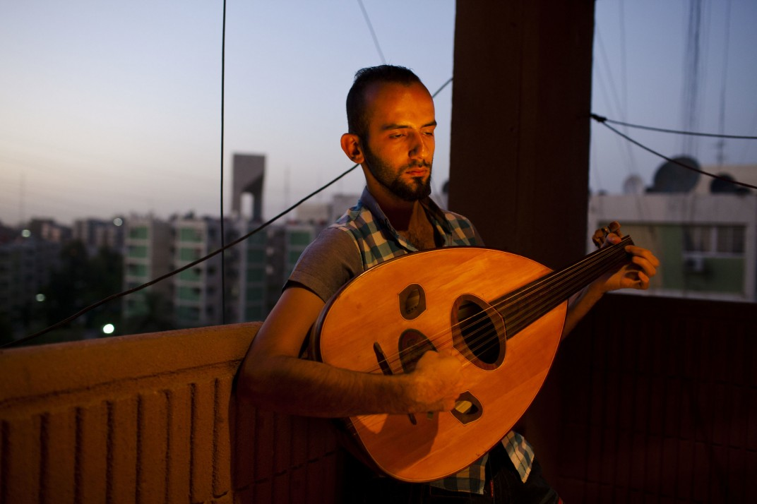 Anmar Hasan (27), a music graduate of the Baghdad Academy of Fine Arts in his apartment in the al Salheya neighbourhood of Baghdad. Since graduating Anmar has made plans to move to Turkey as a refugee. Baghdad, Baghdad, Iraq. July 2 2014. Photo: Ali Arkady / VII